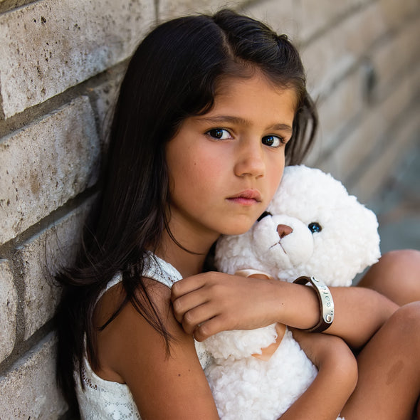 girl wearing safe band holding teddy bear