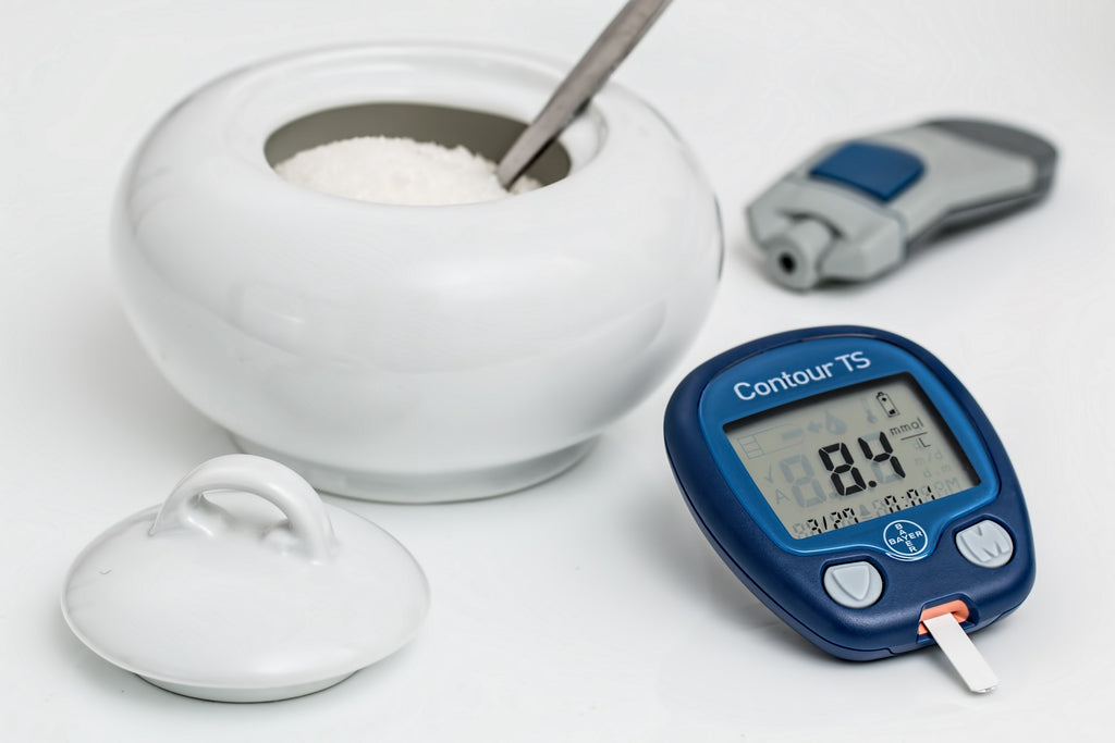 blood sugar monitor and a bowl of sugar
