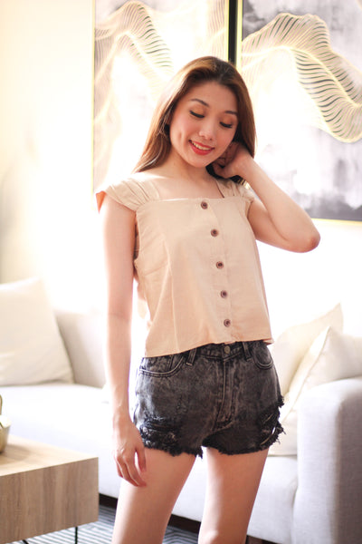 Cream sleeveless with brown button