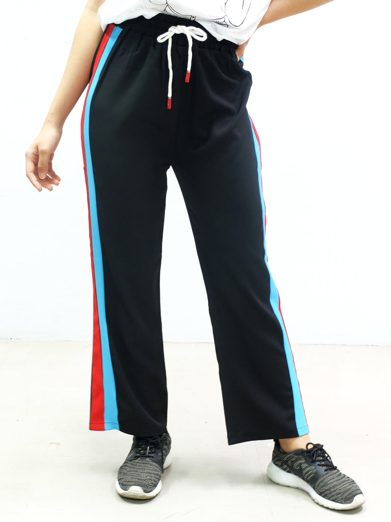 Black track pants with blue and red