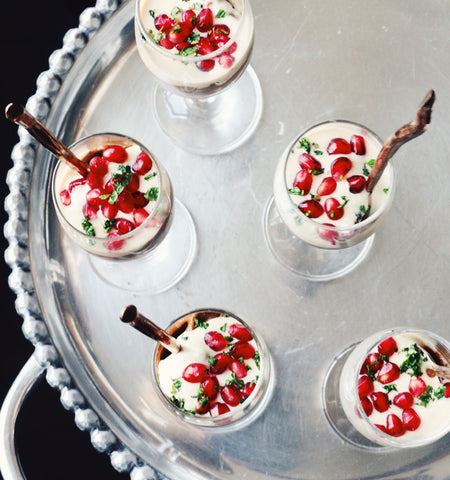avocado pudding garnished with pomegranate seeds in cups on a platter