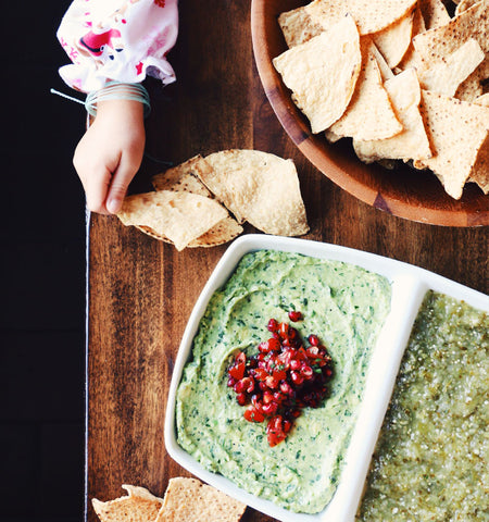 guacamole with pomegranate seeds served with tortilla chips