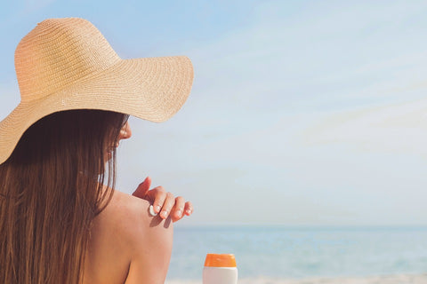 woman applying sunblock on her shoulder at the beach