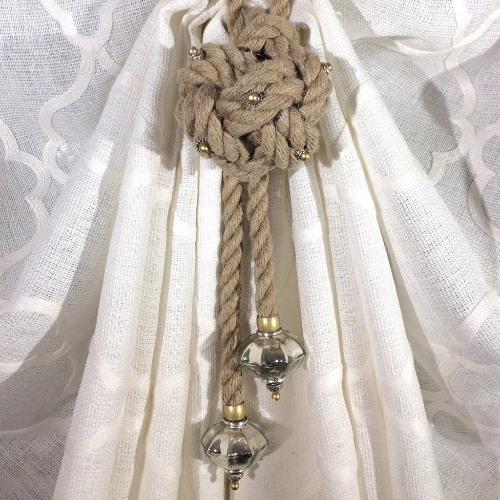 Curtain holdback window hardware made of premium hemp rope embedded with silver and gold beading and mercury glass ornaments.
