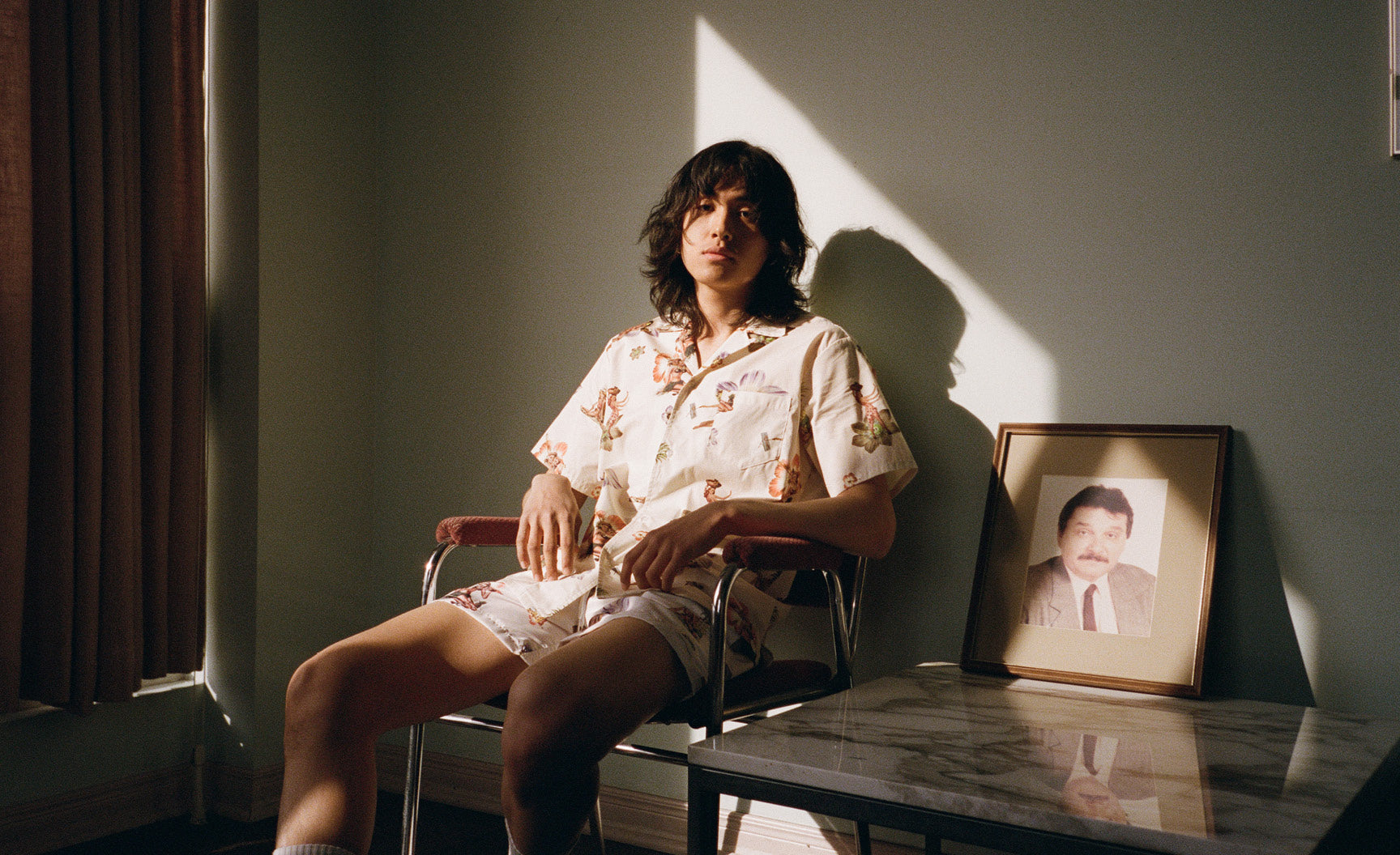 Man wearing Bather camp shirt sitting in chair with sunlight