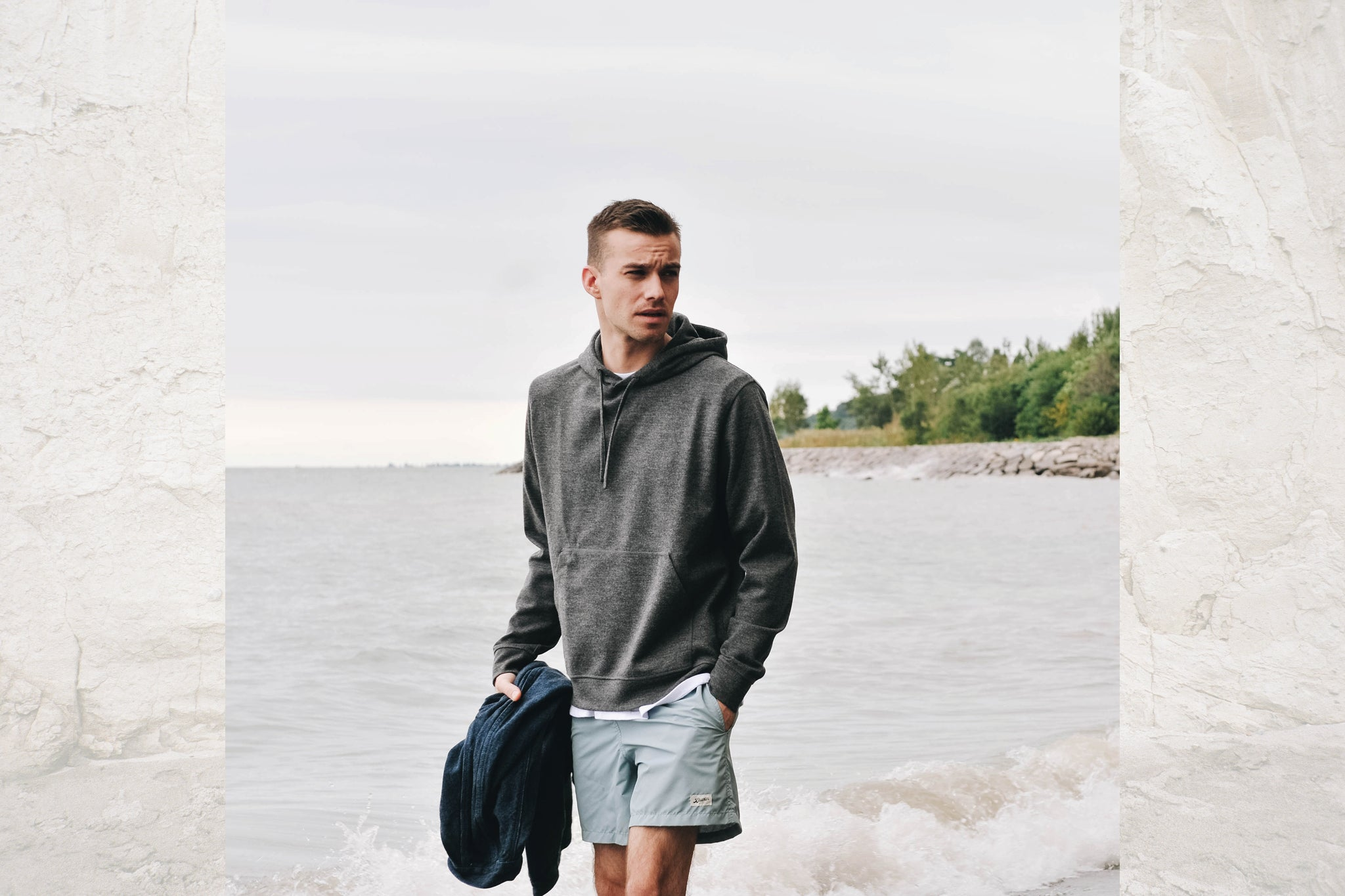 Man wearing swim trunks and a sweater on the beach