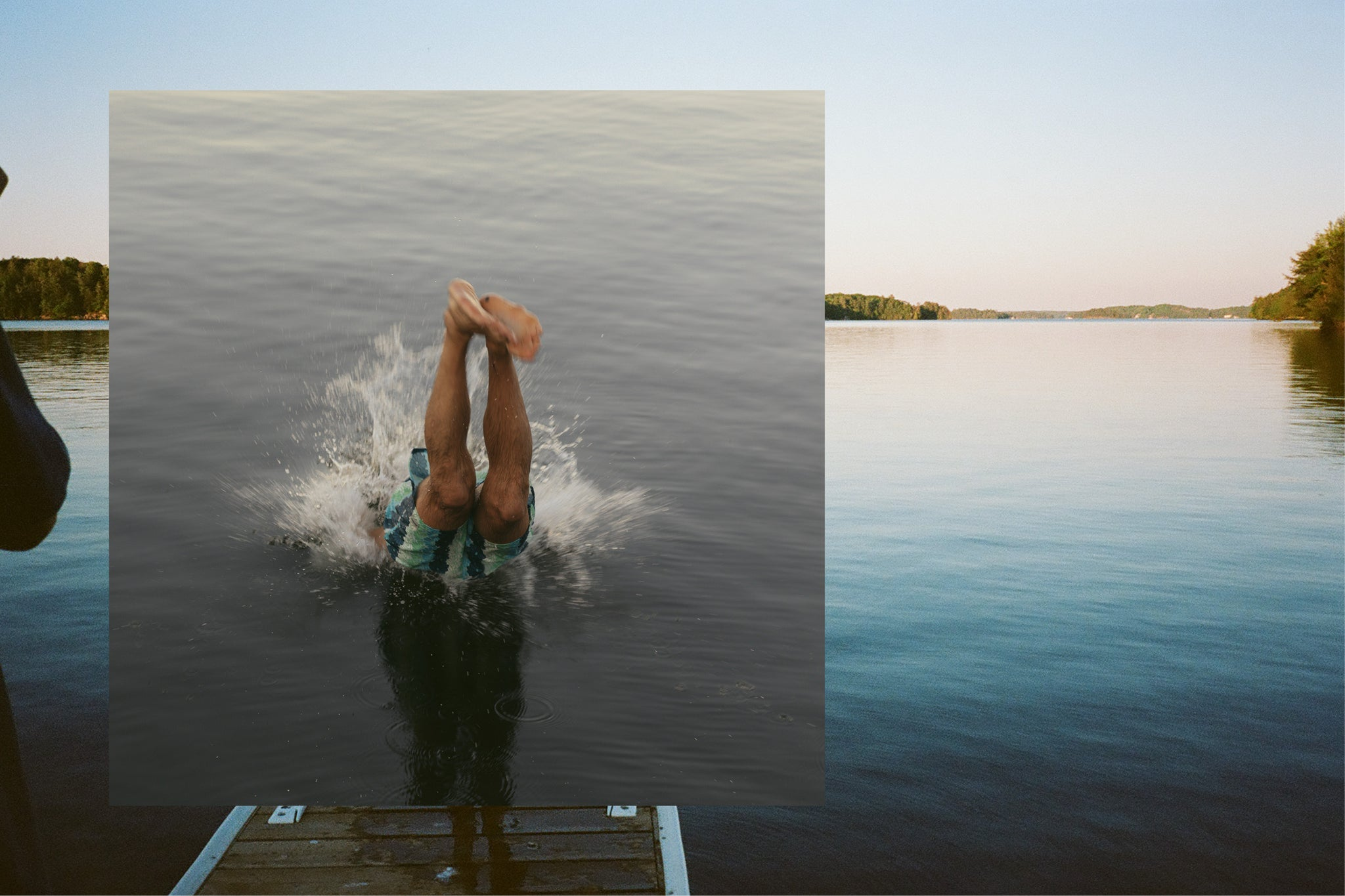 Man diving off a dock into a lake while the sun sets