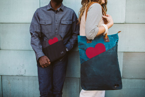 tall tote in rain dark teal and laptop sleeve in cloud gray each with a red valentine heart in open outside pocket