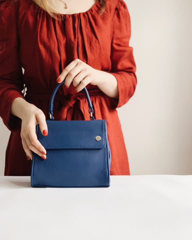 Woman holding leather bag on table