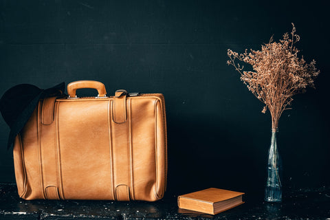 Brown leather bag on black table with brown book and dried flowers