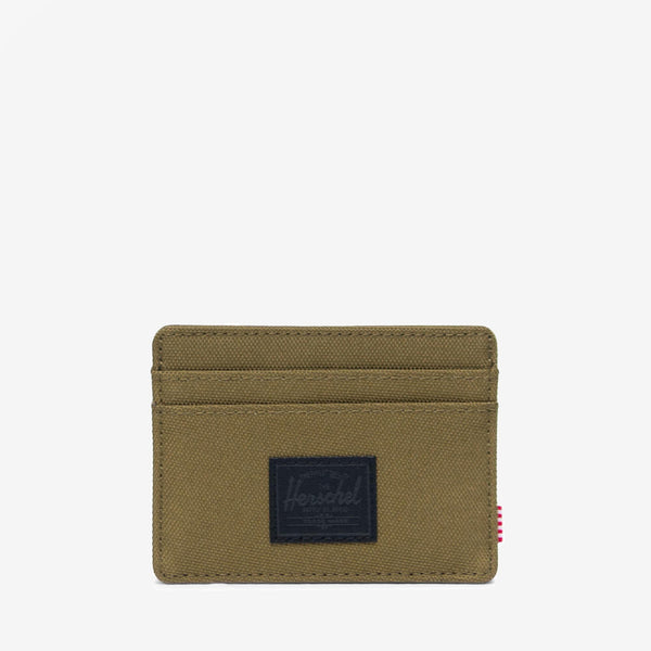 "Featuring a timeless design, the Charlie+ wallet in Khaki Green from Herschel is a compact and convenient card holder.  3""(H) x 4""(W) Signature striped fabric liner / RFID blocking layer Multiple card slots and top-access storage sleeve Engineered red and white striped tab Product code: 10360.03884.OS off the hook oth streetwear boutique canada montreal"