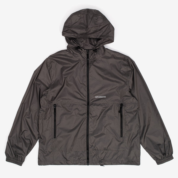 The Tech Ripstop Jacket in Grey from Stussy features a hood with Stussy custom zip pulls throughout. Adjustable hood and hem. Mesh lined. Elastic cuff and Stussy screenprint on front left panel. 100% Nylon Woven  Product code: 115514  off the hook oth streetwear boutique canada montreal