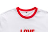 The Love For Sale Ringer Tee in white from Chrystie NYC comes in a cut and sew construction, 180 GSM construction, with a flocking graphic on the center of the chest. Ringer details are rounded out with an eye-catching red trim. Now at OTH.