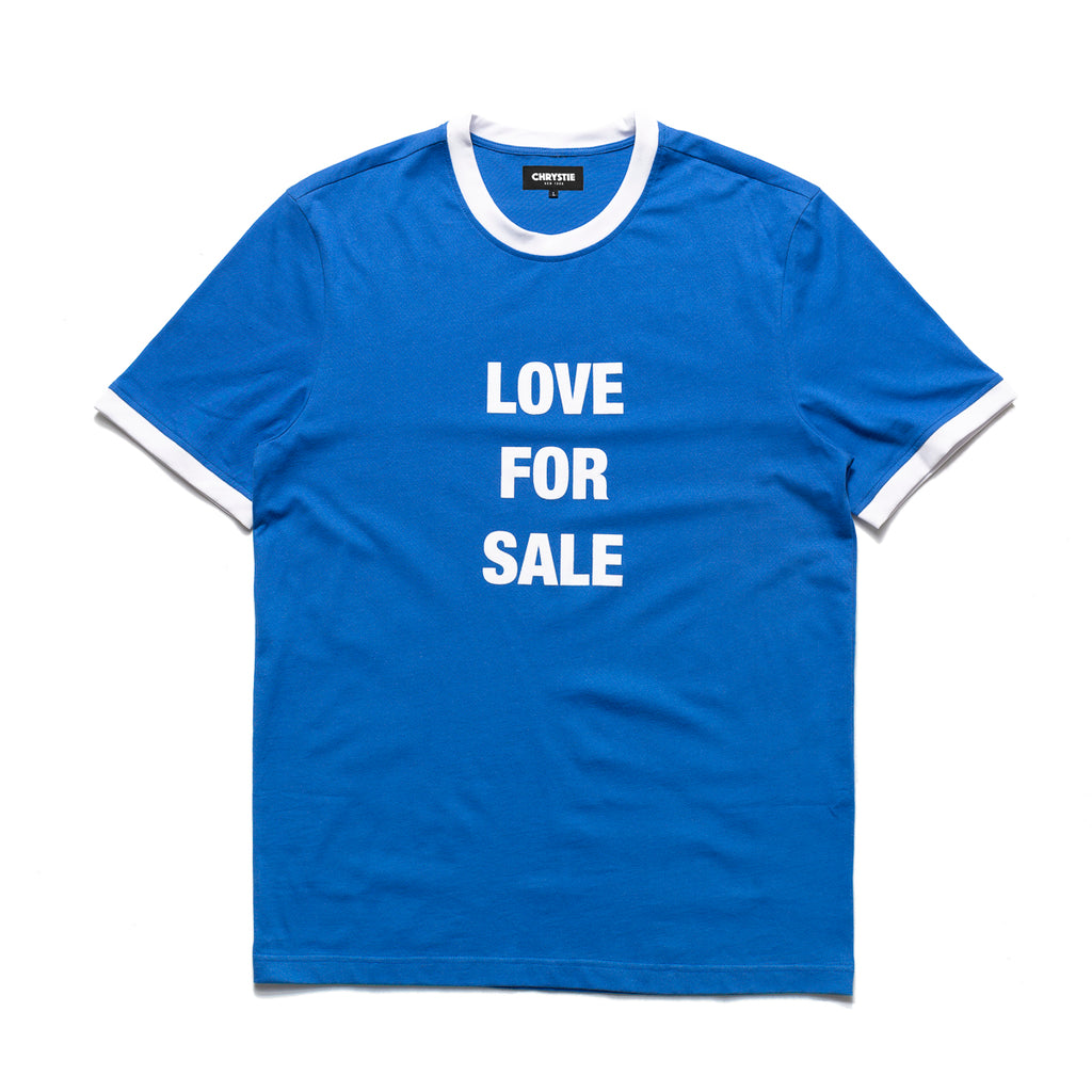 The Love For Sale Ringer Tee in blue from Chrystie NYC comes in a cut and sew construction, 180 GSM construction, with a flocking graphic on the center of the chest. Ringer details are rounded out with an eye-catching white trim. Now at OTH.