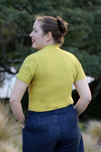 Leimomi, a white woman with her hair in a bun, is shown wearing the Scroop Miramar Top with short sleeves in yellow cotton lycra jersey.  She shows the back view of the top