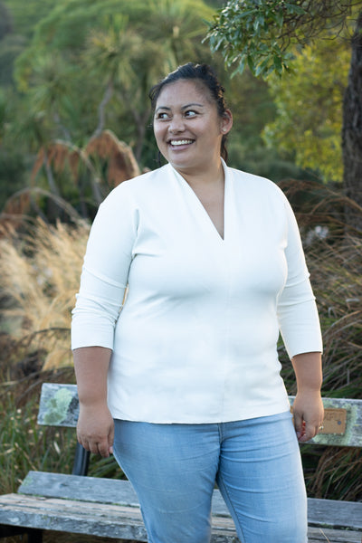 Rose, a Pasifika woman with her hair in a ponytail, is shown wearing the Scroop Miramar Top with 3/4 length sleeves in ivory ponte knit