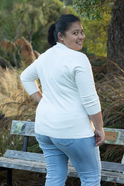 Rose, a Pasifika woman with her hair in a ponytail, is shown wearing the Scroop Miramar Top with 3/4 length sleeves in ivory ponte knit.  She faces away from the camera and looks over her shoulder.