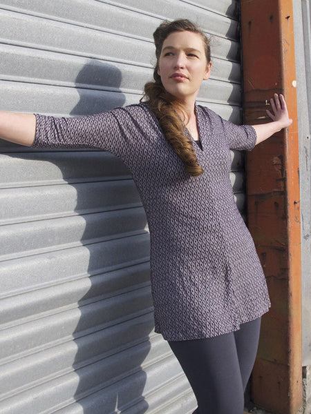 Leimomi, a white woman with her hair in a braid, is shown wearing the Scroop Miramar Tunc with 3/4 sleeves in purple jacquard merino viscose knit.
