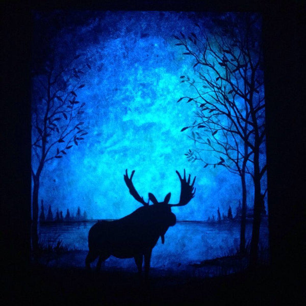 Glow in the dark painting of a moose silhouette with blue glow in the background