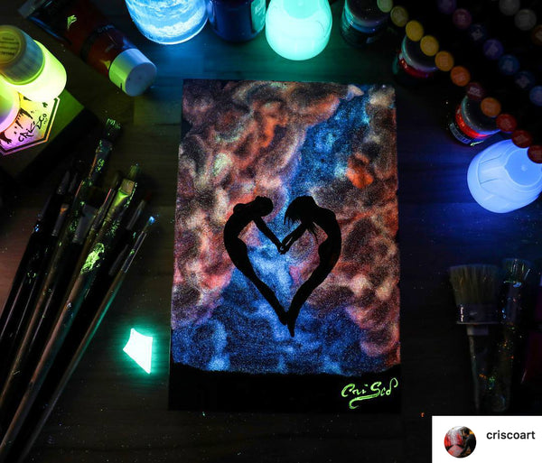 Glow in the dark painting of two women standing together in the shape of a heart