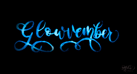 "Blue glow in the dark cursive script that reads ""Glowvember"" on a black background"