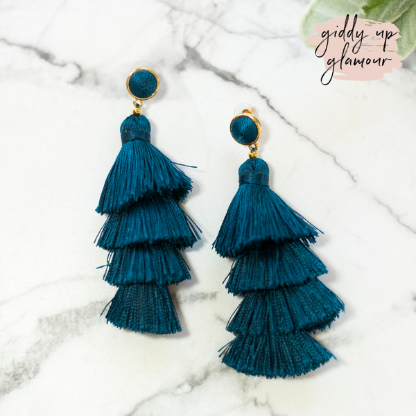 fun and flirty fast fashion long layered fringed tassel earrings with treaded top in dark teal blue on post back with gold accents
