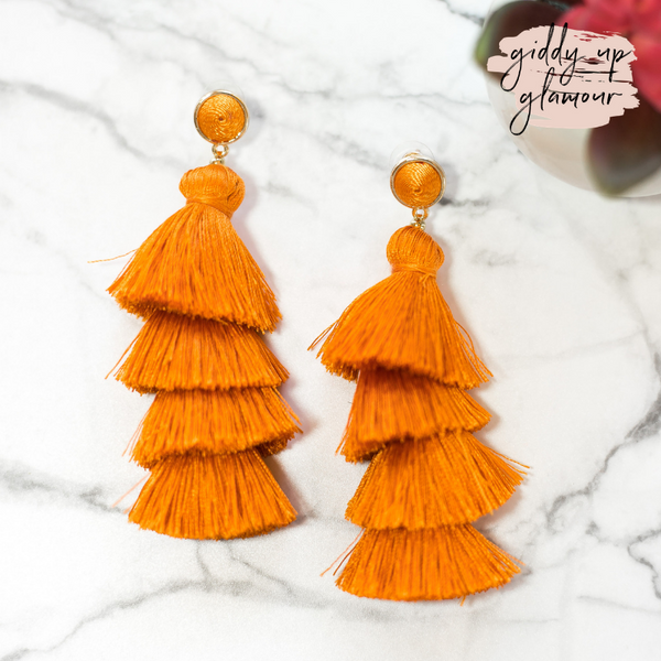 fun and flirty fast fashion long layered fringed tassel earrings with treaded top in orange on post back with gold accents