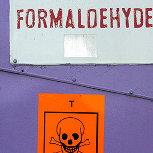 the side of a metal object, maybe a metal barrel, that is labelled formaldehyde and has a skull and crossbones icon visible