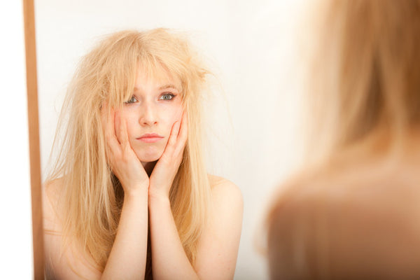 A young blonde woman, head in hands, fed up with her hair as she looks into the mirror.