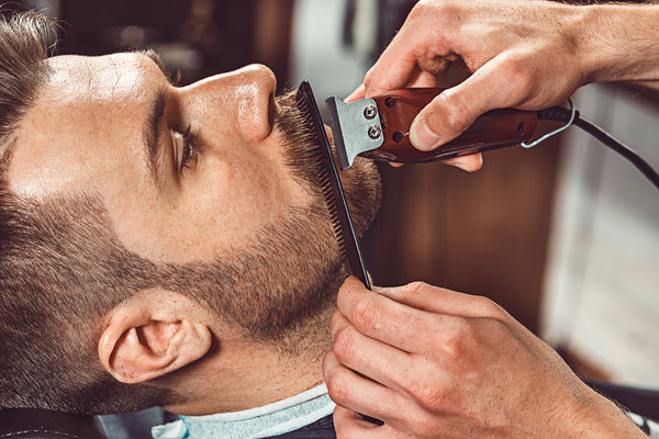 barber trimming beard perfecting beard care routine toppik hair blog