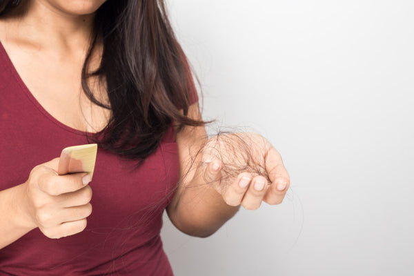 woman brown hair holding comb hair loss shedding hand excess