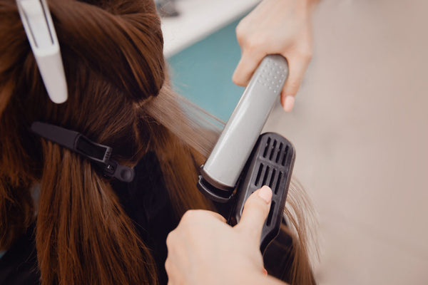 straightening flat iron brown hair close up salon stylist what is keratin toppik hair blog