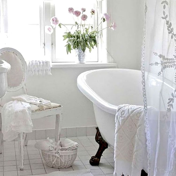 Clean white bathroom with clawfoot tub and sheer curtains