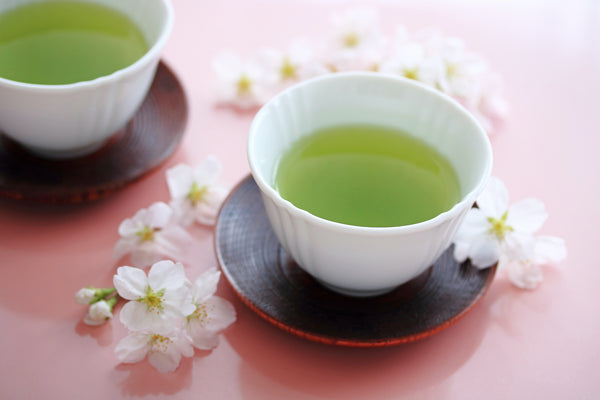 japanese style green tea on pink table with cherry blossoms