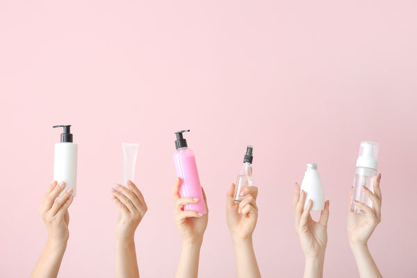 women hands holding lotion bottles cosmetics