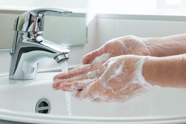 washing hands in clean white bathroom