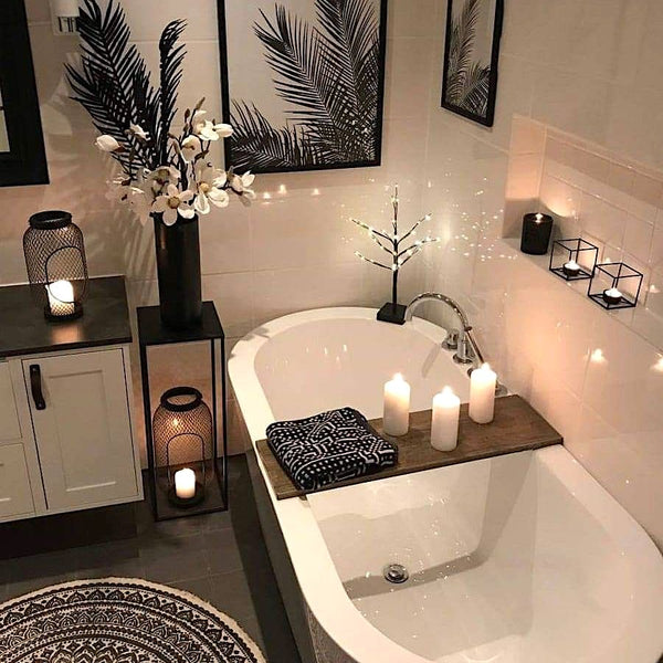 Cozy white bathtub with candles and botanical prints