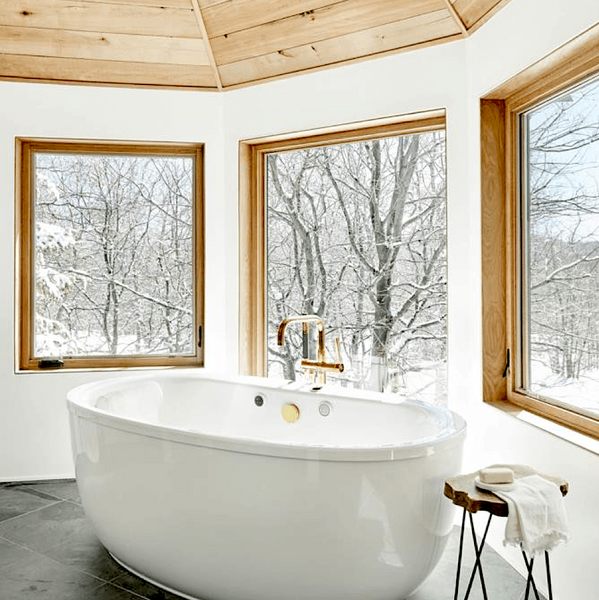 Snowy winter bathroom with large windows and natural wood