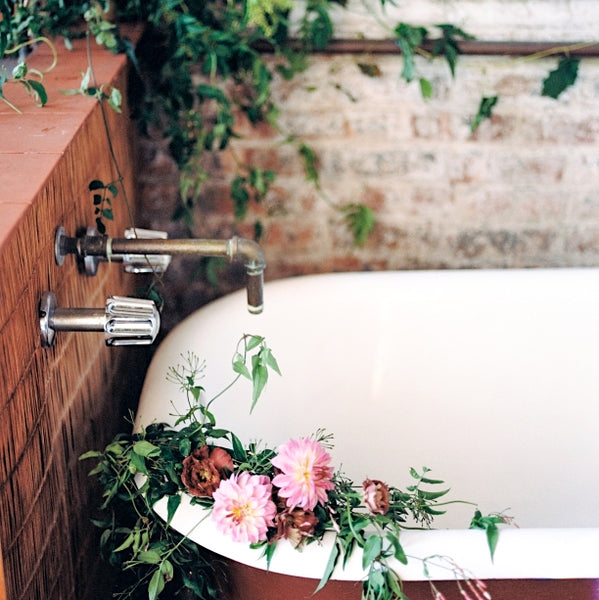Porcelain bathtub with live flowers and brick wall