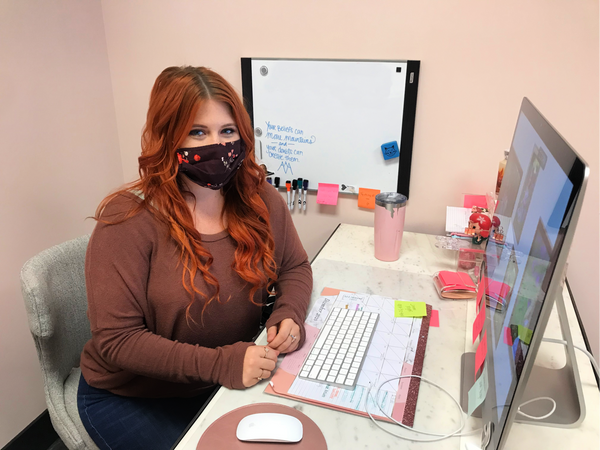 redhead girl sits at desk with computer, wearing face mask