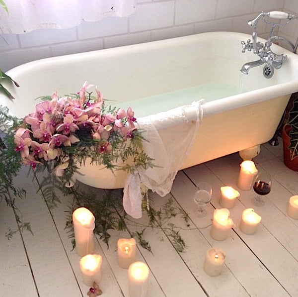 White clawfoot bathtub with flowers and candles