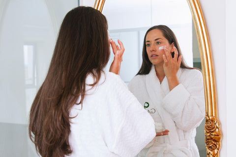 Woman in robe using GAIA spa products