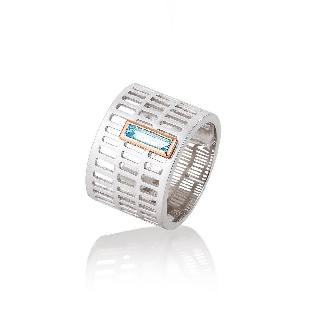 Modern sterling silver ring with rose gold plated accent and an emerald cut blue topaz. By Breuning