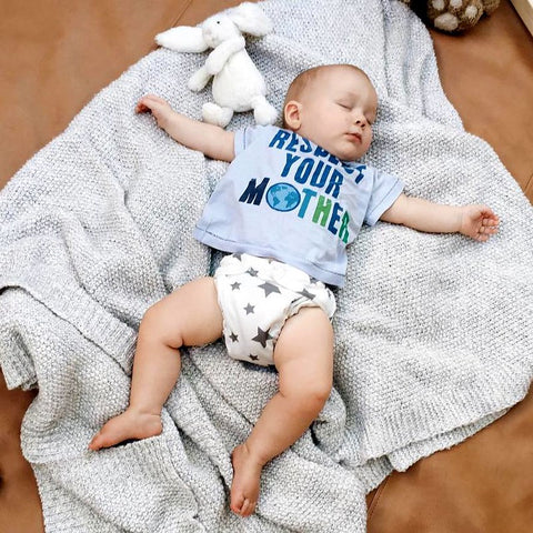 Baby sleeping on a blanke in a Charlie Banana reusable Cloth Diaper and an eco tee shirt