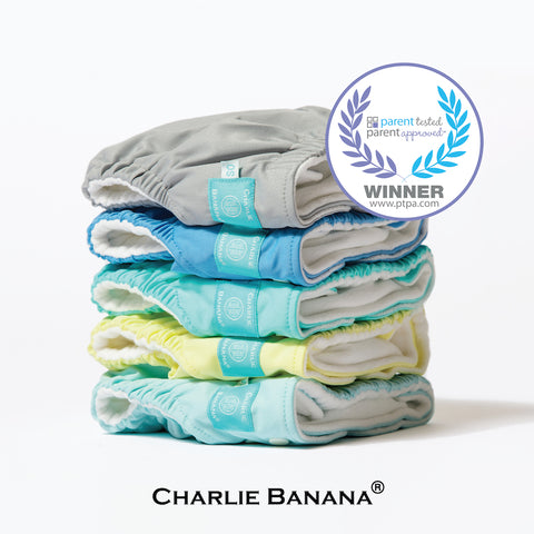A pack of 5 Charlie Banana reusable cloth diapers in solid colors. Parents tested, parents approved.