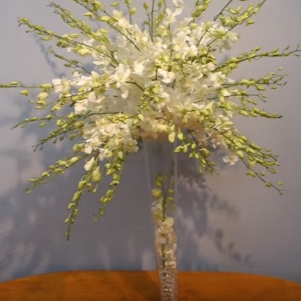 DIY Dendrobium orchids in a tall glass vase centerpiece.