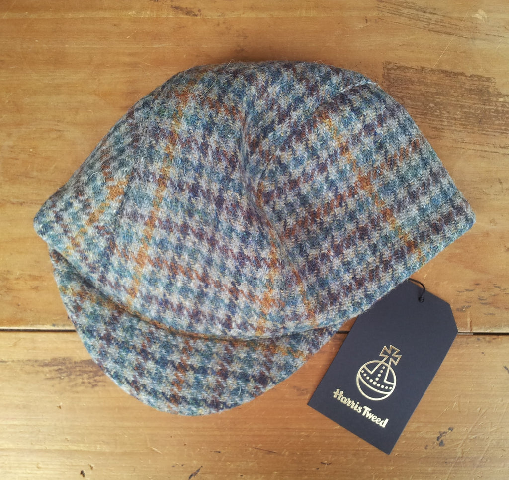 Bespoke made to order cycling cap (all sizes catered for) handmade in wonderful dogtooth Harris tweed in a myriad of greens, purples, and gold. HORWEEN leather strap. AmiCharnel.