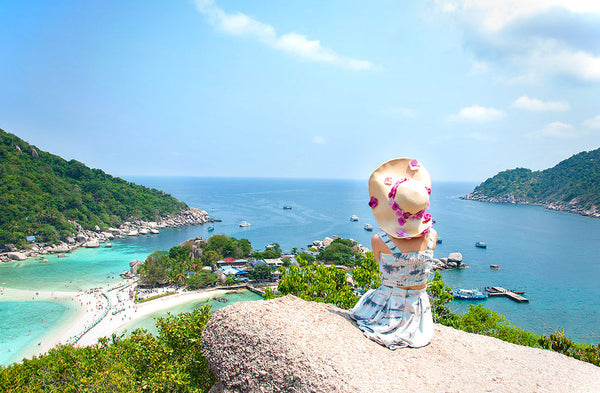 Woman In Two Piece Floral Print Dress Overlooking The Ocean On A Rock
