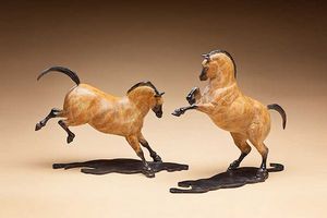 bronze sculptures of two horses, one rearing and one bucking