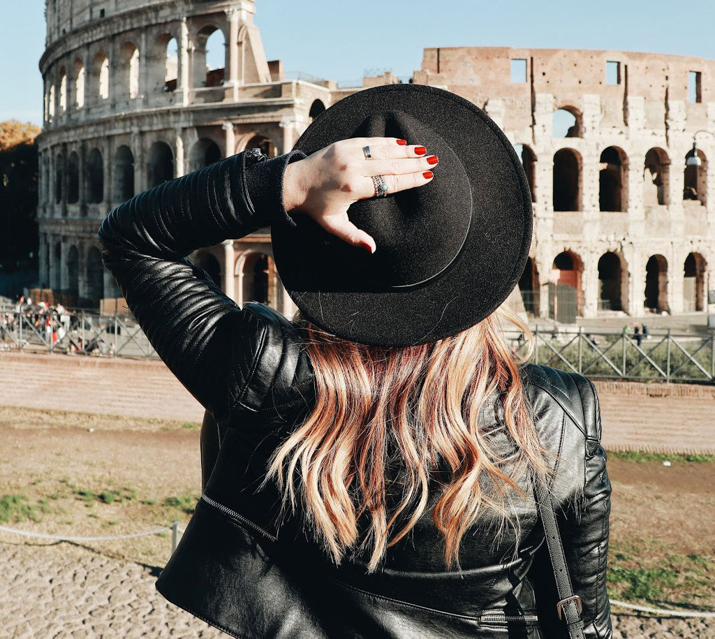 Girl standing in front of Colosseum with back to the camera
